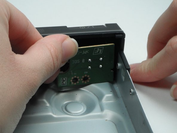 Image 3/3: Pull the shorter button circuit board out of its position.
