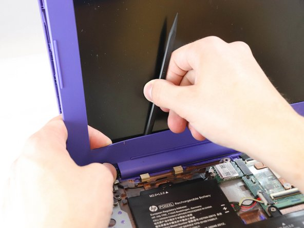 When you get to the bottom of the screen, place the plastic spudger between the screen and the frame and drag along the bottom to separate the adhesive.
