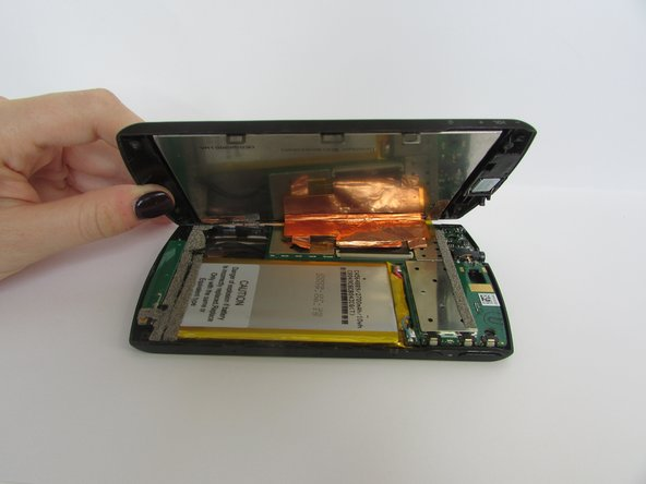 Image 1/2: Unplug the touch pad from the motherboard. Do this by applying pressure on the thin black piece(attached at the bottom of the metallic foil) Press the plastic spudger against the thin black piece and  release it.