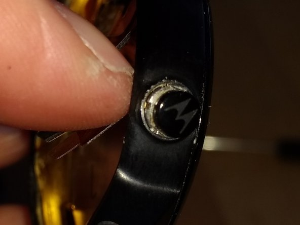 Use a small six pin spanner to unscrew the button from the case.