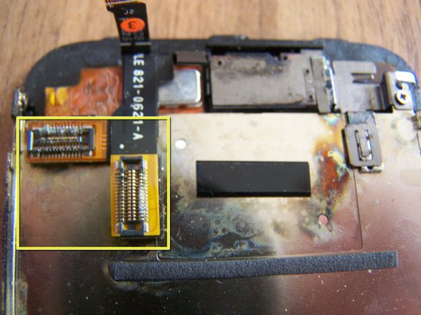 The rear of the display assembly shows more green corrosion and debris on the LCD and digitizer connectors.