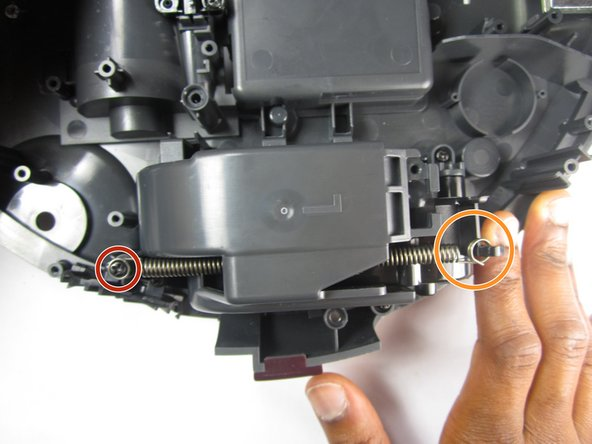 Image 1/2: Then undo the spring from the plastic hook to completely remove it from the wheel assembly.