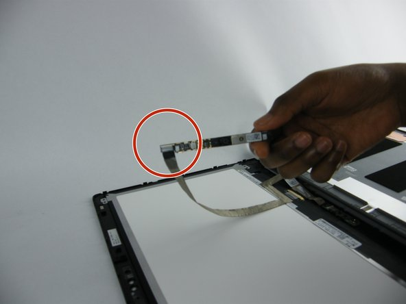 Carefully remove the ribbon cable that holds the webcam to the screen, then unplug the webcam from the ribbon cable.