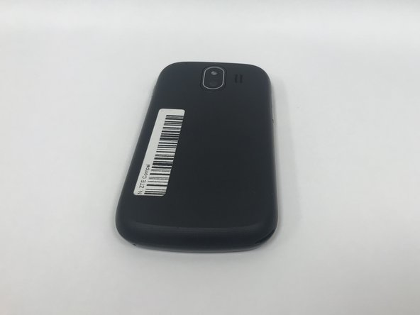 Place the phone on a flat surface with the screen facing down. This will allow easy access to  the removable black plastic cover on the back of the phone.