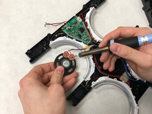 Use a soldering iron to desolder the red and black speaker wires from the speaker.