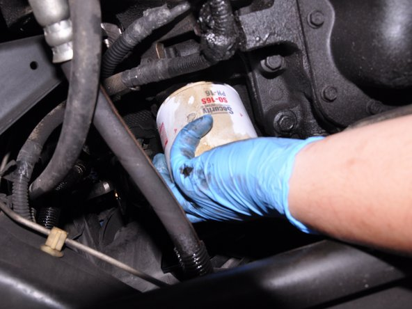 Turn the oil filter counter-clockwise by hand until it comes off the engine's oil filter threads.