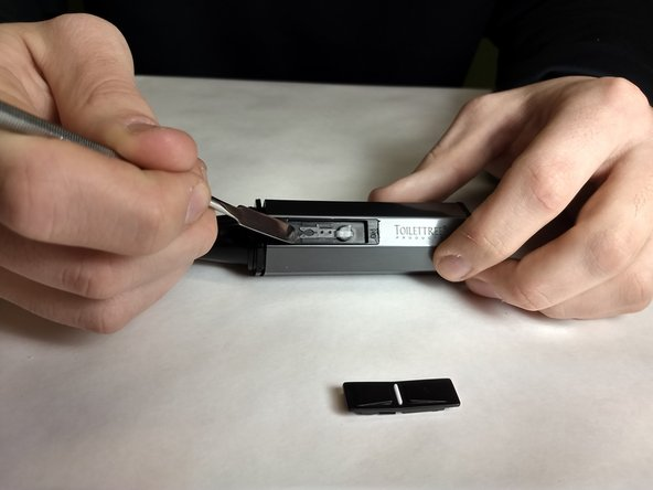 Continue disassembly by prying the clear tab upwards.