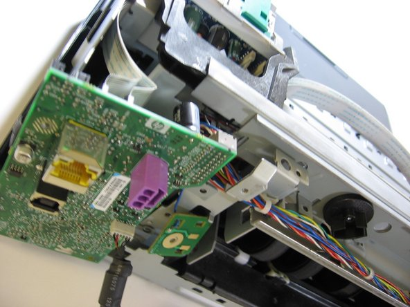 Now that the motherboard has been dislodged from its housing, you can begin removing the screws from the motor carriage.