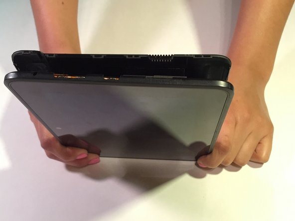 Using the plastic opening tool, start from one corner and go around the Kindle Fire using the tool in a down and up motion to continue to pop off the backing.