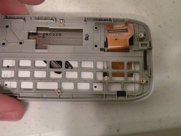 Image 2/3: Now, lift it off, threading the Screen/Number Pad Cable Through the hole.