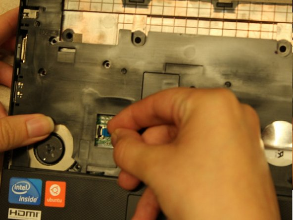 Gently lift up on the black plastic tab that is securing the blue tab in place.