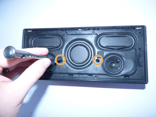 Image 2/2: Take the 2 20mm Philips J1 screws out of the middle of the speaker as shown.