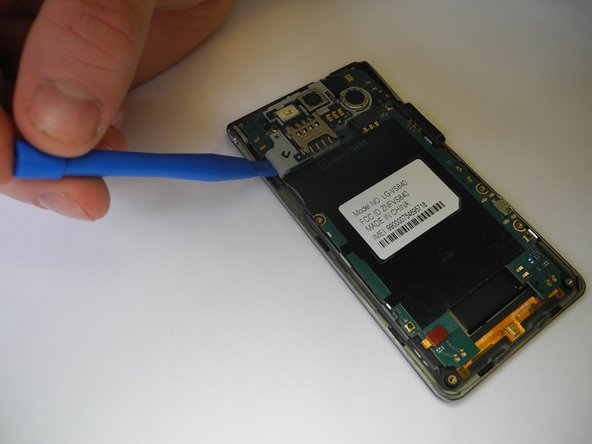 Remove SIM card holding by prying it with opening tool. As you are lifting it, disconnect the ribbon that is connecting the sim card holding and the rest of the phone.