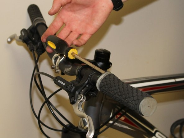 Use a flathead screwdriver to wedge a gap between the grip and the handlebars.
