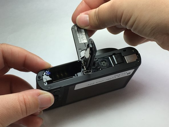Once the part is separated, move it toward the battery slot.