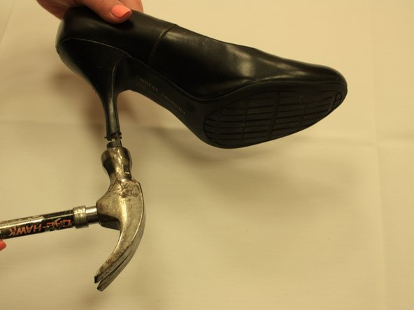 Gently tap the new tip in with the hammer. Careful not to damage the shoes material.