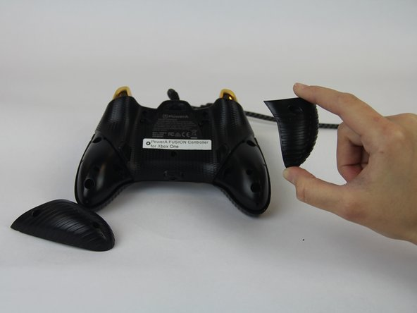 Remove the two bottom plastic grip covers.