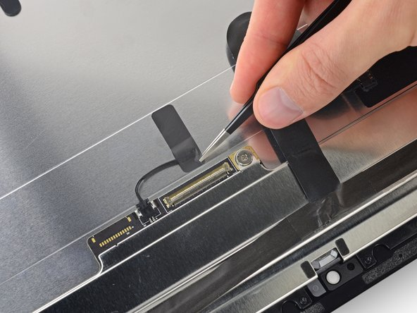 Peel up the piece of tape securing the thermal sensor to the back of the display assembly.