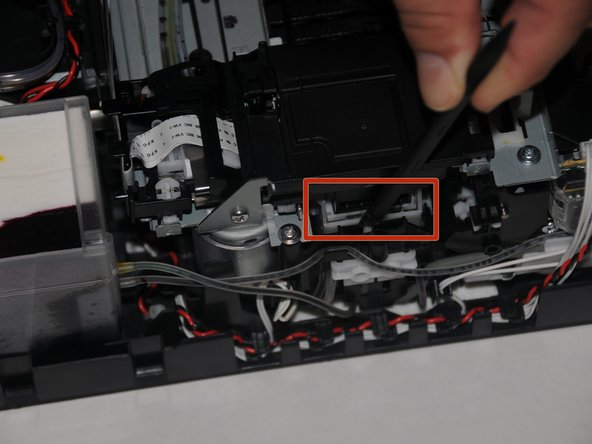 Using a spudger, press down on the plastic housing of the carriage that the print head rests on.