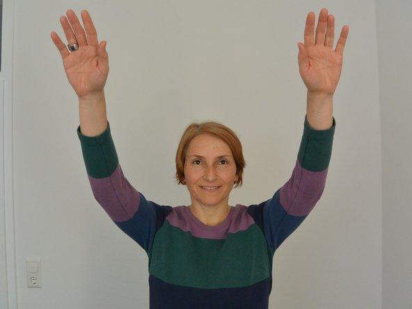 Locker stehen, schwinge Deine Arme sanft von oben nach unten. Du wählst selbst wie groß die Bewegung ausfällt. Gerne kannst Du Deine Knie dabei mit beugen und strecken.