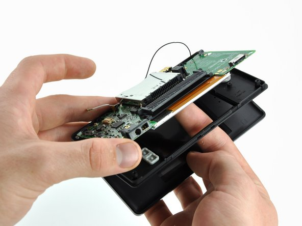Open the display enough to use your finger to push the front edge of the motherboard up and away from the upper case.