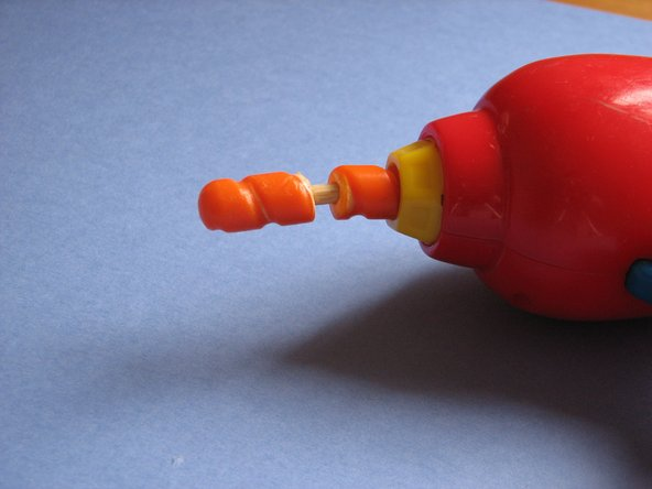 Insert the other end of the wooden dowel into the other end of the plastic toy.