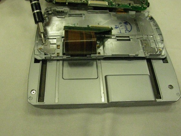 Remove the keyboard by unscrewing the two pairs of silver Torx head screws that run along the sliding tracks.