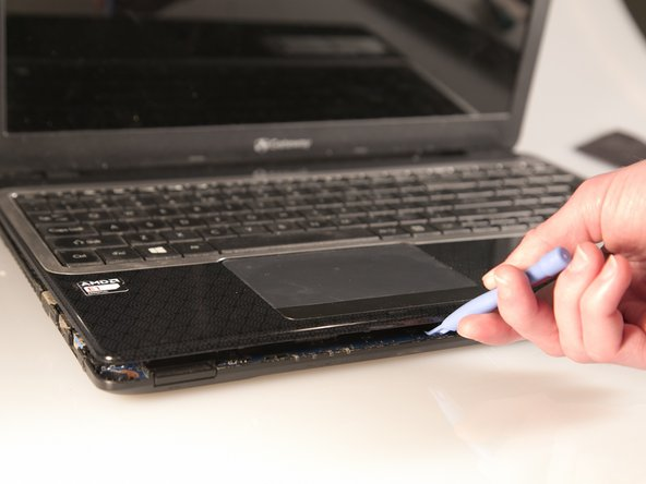 Separate the bottom panel from the touchpad assembly by inserting a plastic opening tool between them on all four sides.
