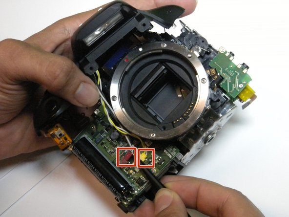Use the tweezers to disengage the yellow and red wires from the camera body.