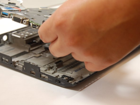 Carefully detach the motherboard (black plastic) from the laptop.