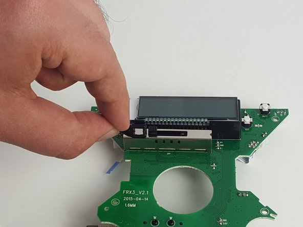 On the back of the motherboard, just below the LCD screen, gently pull up on the small, black plastic switch to remove it.