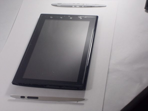 Remove silver side panels with prying tool by snapping them of the outer casing of the tablet.