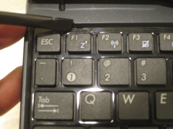 Turn the tablet over and open it up. Insert a nylon spudger into the slots above F1, F6, F10 to pry up the keyboard.