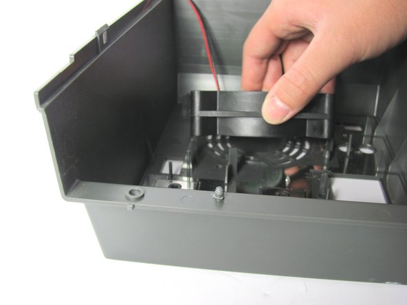 Remove the fan by lifting it gently away from the back panel.