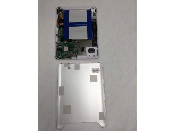 Place the device screen down on the table and use a pry tool to remove the back panel.
