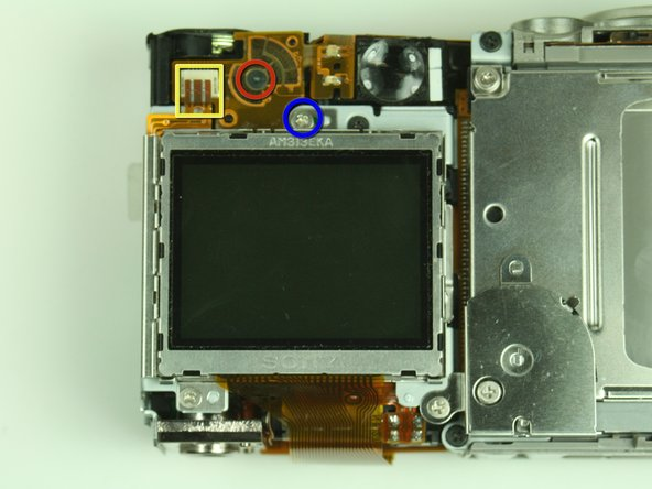 On the backside of the camera, remove the 3.5 mm screw that sits to the left of the viewfinder and above the LCD screen.