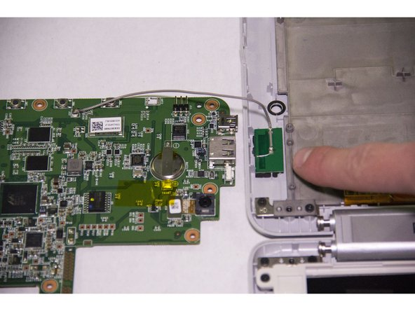 The motherboard is now connected in only one place on the edge of the device. Being careful of this, flip the motherboard outside of the device, leaving it connected to the foam padding inside of the device.