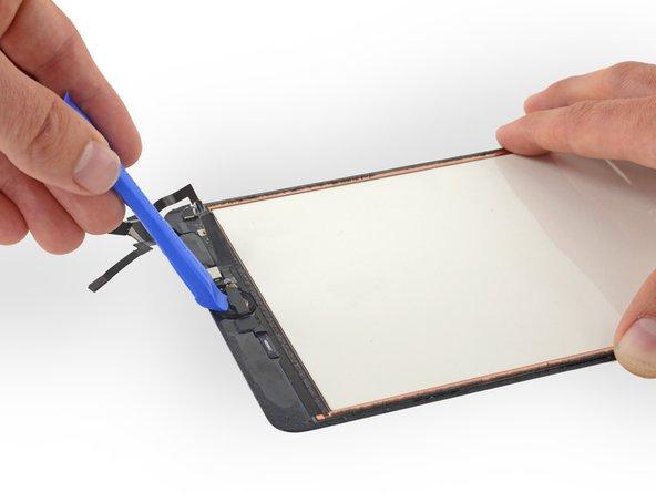 プラスチック製の開口用ツールを使って、ホームボタンブラケットをデジタイザの背面から持ち上げてください。