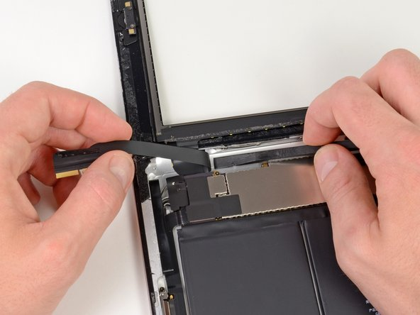 Peel back the touchscreen ribbon cable and use the flat end of a spudger to release the adhesive securing the cable to the rear aluminum case.