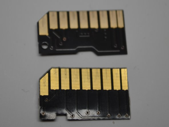 The Nifty MiniDrive chip has a red glue substance. And a square shape cut up into bottom, this seats the chip in place in the plastic mold