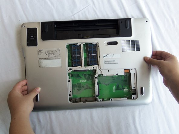 Holding the opening from the optical drive in one hand and the other hand on the opposite side of the laptop, lift and remove the back cover assembly.