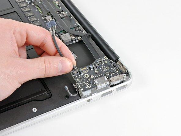 Hebe das I/O Board vorsichtig von der Ecke her an, die dem Logic Board am nächsten ist, und entferne sie vom oberen Gehäuseteil.
