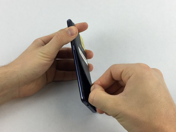 Remove the rear cover using your hands at the lip on the device back cover. No tools required.