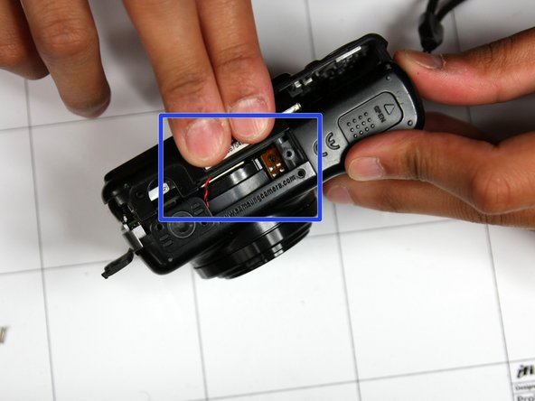 Squeeze area noted by blue square and pull outside shell apart from remaining camera.