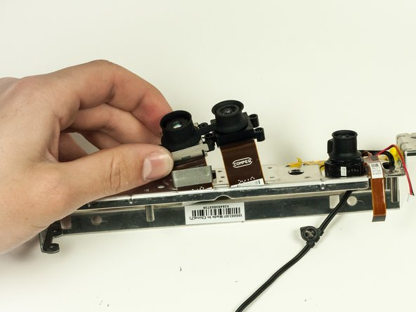 Remove the two cameras on the left (which are connected) by pulling their ribbon cables through their respective slots.