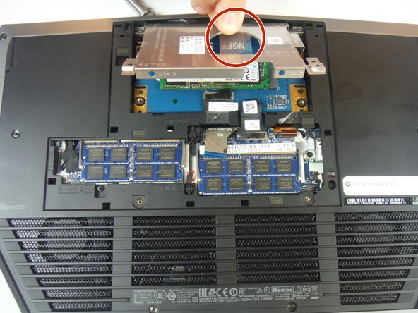 Grab the pull tab to pivot the solid-state drive bracket upwards. Remove the bracket from the computer base.