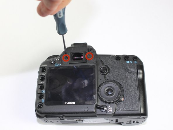 Remove each 6.3 mm screw on either side of the viewfinder using a Phillips #0 screwdriver.