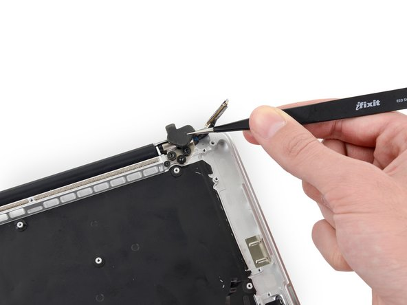Use a pair of tweezers to lift the rubber hinge covers up off the right and left display hinges.