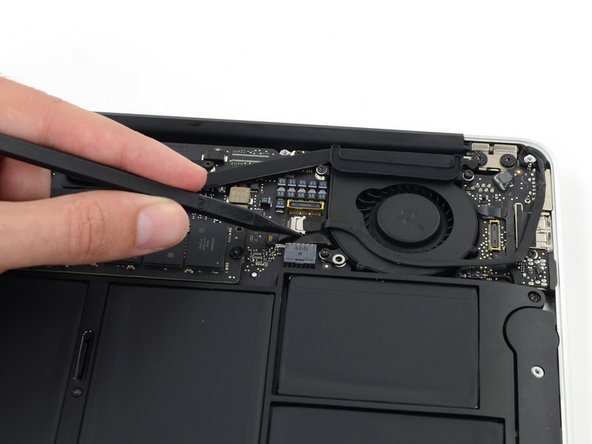 Use the tip of a spudger to carefully push on each side of the iSight camera cable connector to loosen it out of its socket on the logic board.