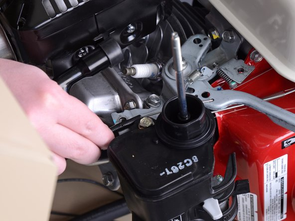 Lift the throttle cable up and pull it the end of the cable out of the hole it hooks into.